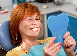Woman examining her smile in the mirror