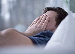 Frustrated man in bed covering his face